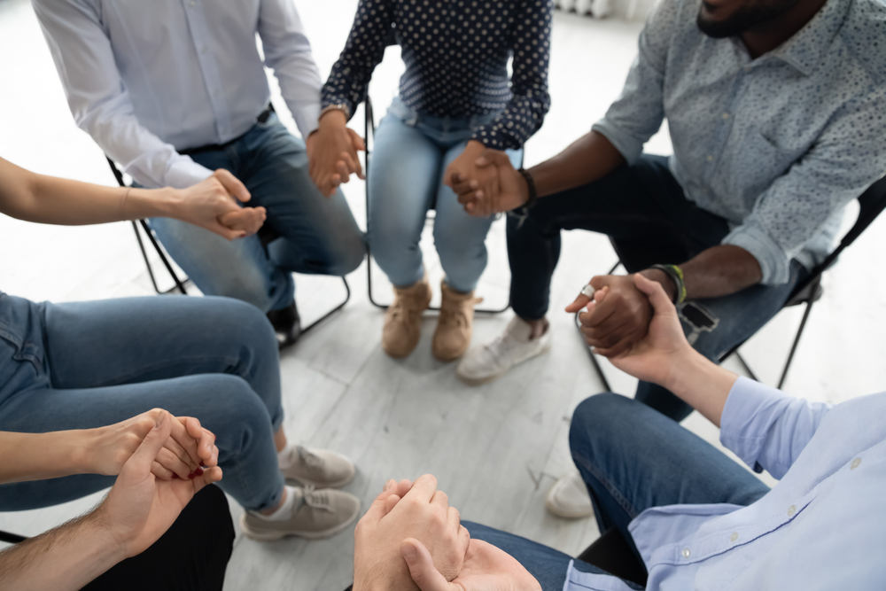 People,Sit,In,Circle,Hold,Hands,Involved,At,Group,Therapy