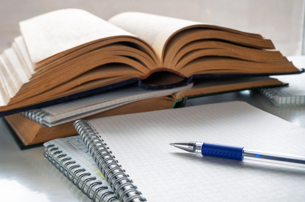 The,Pen,Lies,On,A,Blank,Sheet,Of,Notebook.,Nearby
